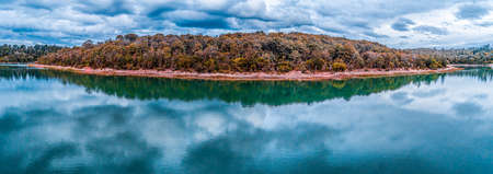 Wide beautiful panorama of trees growing on lakeshore with scenic clouds reflections in the water