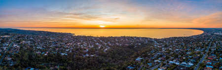 Scenic aerial view of Port Phillip Bay at sunset surrounded by residential area. Melbourne, Australia