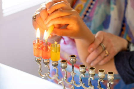 Woman hands helping a child to light Hanukkah candle