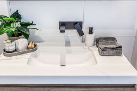 Closeup of modern white washbasin with black faucet