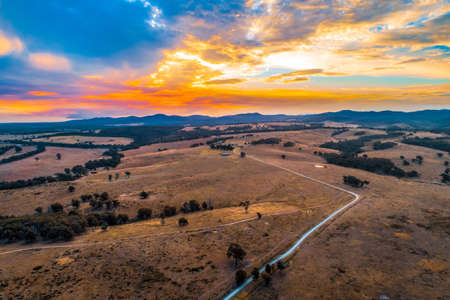 Rural dirt road passing through pastures towards hills silhouettes at sunset - aerial view