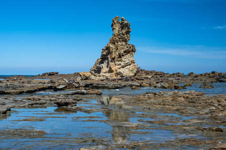 Eagles Nest rock reflecting in puddles at high tide in Victoria, Australia