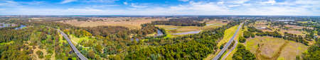 Wide aerial panorama of A440 highway and scenic countryside near town of Sale in Victoria, Australia