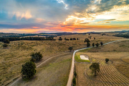 Sunset over fields and hills - aerial view 写真素材