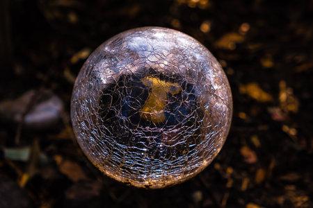 Closeup of garden light sphere made of broken cracked glass on blurred background 写真素材