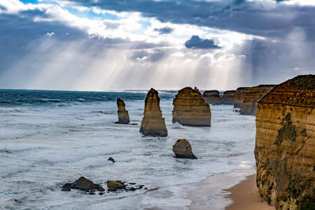 Closeup view of the 12 Apostles rock formations under sun rays and stormy sky in Victoria, Australia