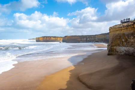 Tourists looking at amazing views of rugged cliffs on the coastline. Great Ocean Road, Victoria, Australia