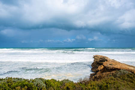 Stormy clouds over strong ocean waves breaking over cliffs in Victoria, Australia