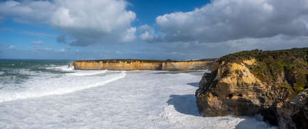 Wide panorama of limestone cliffs over ocean waves on Great Ocean Road, Victoria, Australia