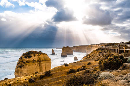 Sun rays through clouds shining on the Twelve Apostles rock formations on Great Ocean Road, Victoria, Australia