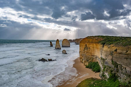 Sun rays shining through stormy clouds on the Twelve Apostles rock formations on the Great Ocean Road in Victoria, Australia