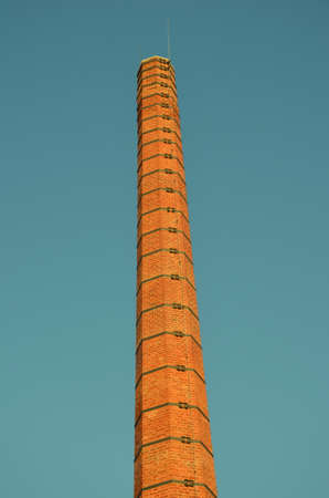 carbon emission: smokestack factories. Orange construction. blue sky. Harmful to the environment. tall chimneys. Stock Photo