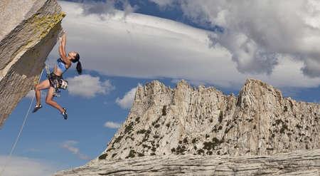 용감: 여성 바위 산악인 도전 절벽의 가장자리에 그녀의 다음 그립에 도달하기 위해 투쟁. 스톡 사진