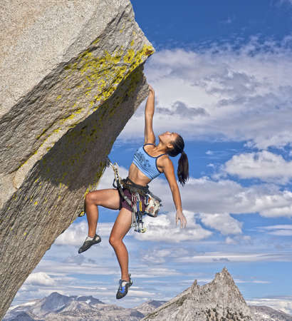 edges: Female rock climber struggles to reach her next grip as she battles her way up a steep cliff.