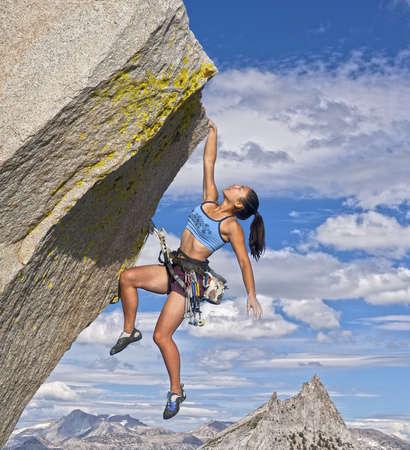 climber: Vrouw bergbeklimmer worstelt om haar volgende greep te bereiken terwijl ze vecht haar weg van een steile klif.