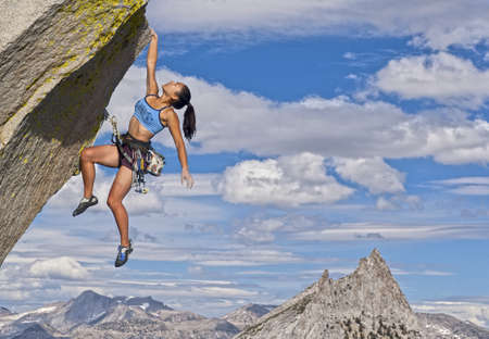 committed: Female rock climber struggles to reach her next grip as she battles her way up a steep cliff.