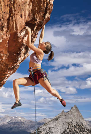 Female rock climber struggles to reach her next grip  on the edge of a challenging cliff. photo