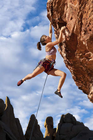 challenges: Female rock climber struggles to reach her next grip  on the edge of a challenging cliff. Stock Photo
