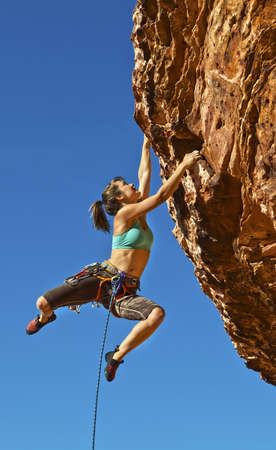 Female rock climber struggles for her next grip dangling on the edge of a steep cliff.