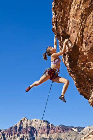 extreme: Female rock climber dangling on the edge of a steep cliff struggles for her next grip.