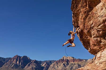 climber: Vrouw bergbeklimmer bungelend aan de rand van een steile klif strijdt voor haar volgende grip. Stockfoto