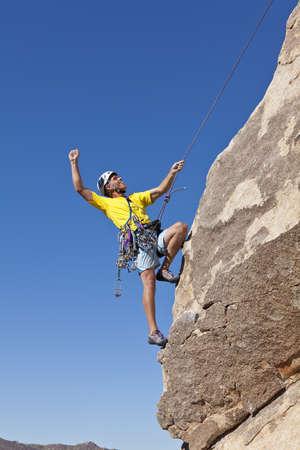 Male rock climber celebrates after a successful ascent. photo