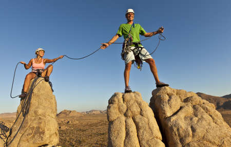 Team of rock climbers struggle to the summit of a challenging cliff. photo