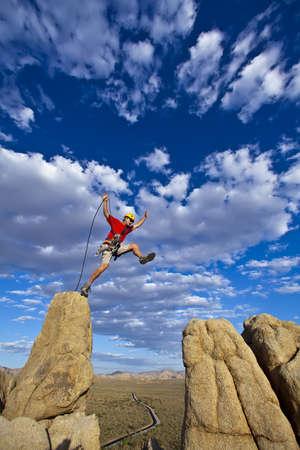 pin�culo: Escalador Mujer salta a trav�s de una brecha en la cima de un pin�culo con un cielo lleno de nubes detr�s hiim. Foto de archivo