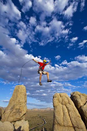saltar la cuerda: Escalador Mujer salta a trav�s de una brecha en la cima de un pin�culo con un cielo lleno de nubes detr�s hiim. Foto de archivo