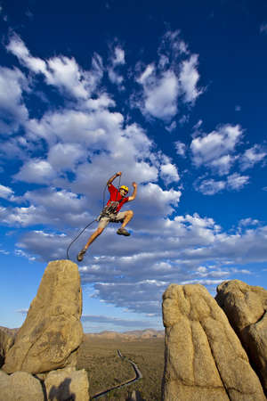 tenacity: Male rock climber leaps across a gap on the summit of a pinnacle with a cloud filled sky behind hiim. Stock Photo