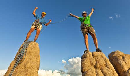 pin�culo: Equipo de los escaladores celebrar en la cima de un pin�culo de roca despu�s de un exigente ascenso.