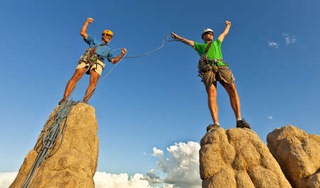 Team of climbers celebrate on the summit of a rock pinnacle after a challenging ascent. Stock Photo