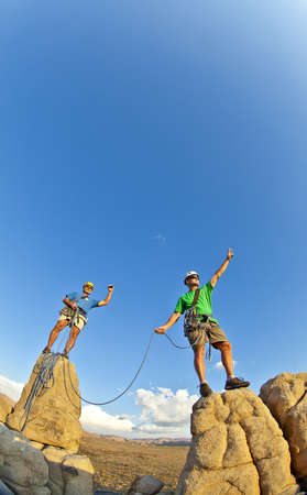 Team of climbers celebrate on the summit of a rock pinnacle after a challenging ascent. photo