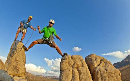 pinnacle: Team di scalatori lottare per il vertice di un pinnacolo di roccia dopo una salita impegnativa.