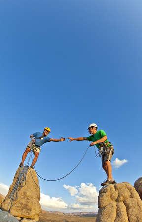 pin�culo: Equipo de alpinistas luchan por la cima de un pin�culo de roca despu�s de un exigente ascenso. Foto de archivo