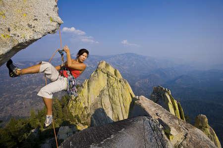 inspiratie: Vrouwelijke klimmer abseilen vanaf de top van een overhangende klif.