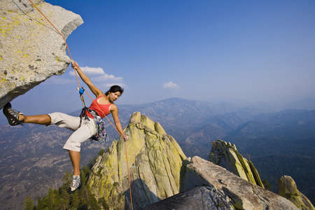 Female climber rappelling from the summit of an overhanging cliff. photo