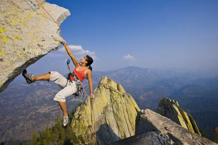 tenacity: Female climber rappelling from the summit of an overhanging cliff.