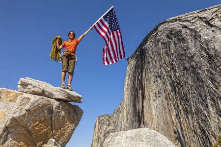 Female climber waves a flag on the summit after a challenging ascent  Stock Photo - 13614802