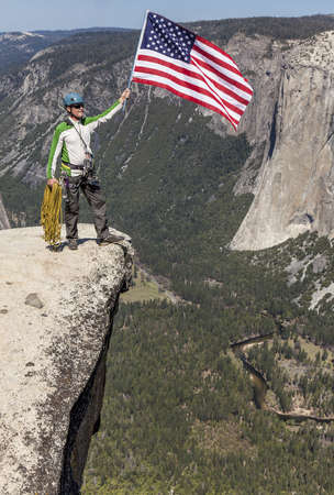 Climber peers over the edge of an abyss in Yosemite National Park, Stock fotó
