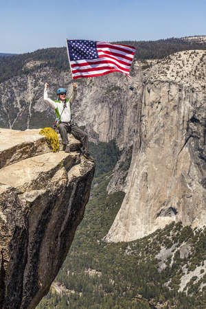 Male climber waves an American flag on the summit of a mountain. Stock Photo - 13614804