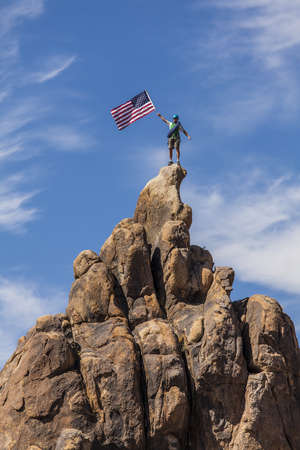 Male climber waves an American flag on the summit of a mountain. Stock Photo - 13614775
