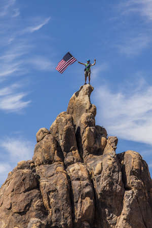 Male climber waves an American flag on the summit of a mountain. Stock Photo - 13614772