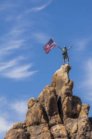 Male climber waves an American flag on the summit of a mountain. photo