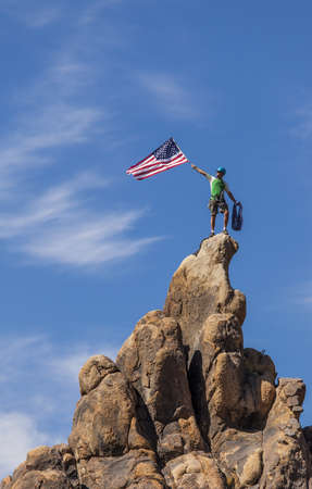 Male climber waves an American flag on the summit of a mountain.