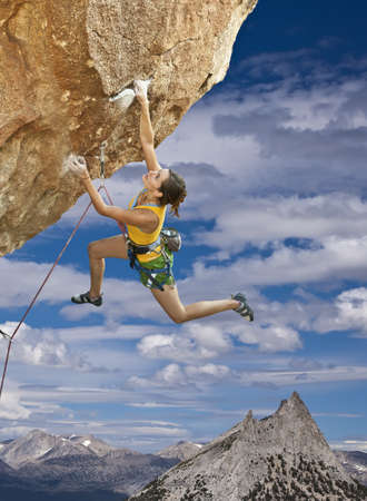 tenacity: Female rock climber struggles to reach her next grip  on the edge of a challenging cliff. Stock Photo