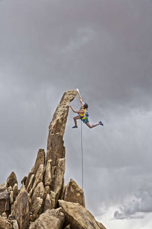 Female rock climber struggles to reach her next grip as she battles her way up a steep cliff in Joshua Tree National Park, California. photo