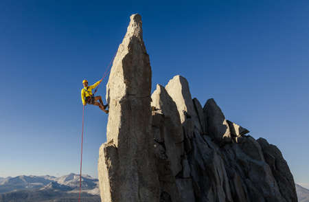 Climber rappells from the summit during a challenging and successful ascent. Stock Photo - 17870673