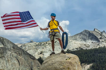 Rock climber raises the flag on the summit after a successful and challenging ascent. Banco de Imagens