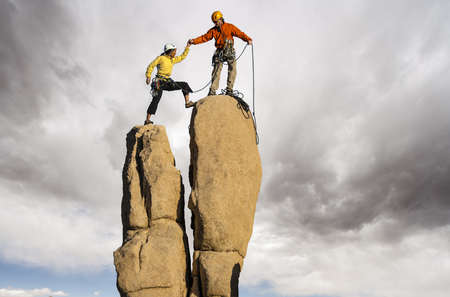 Team of climbers struggle to the summit of a challenging pinnacle. Stock Photo